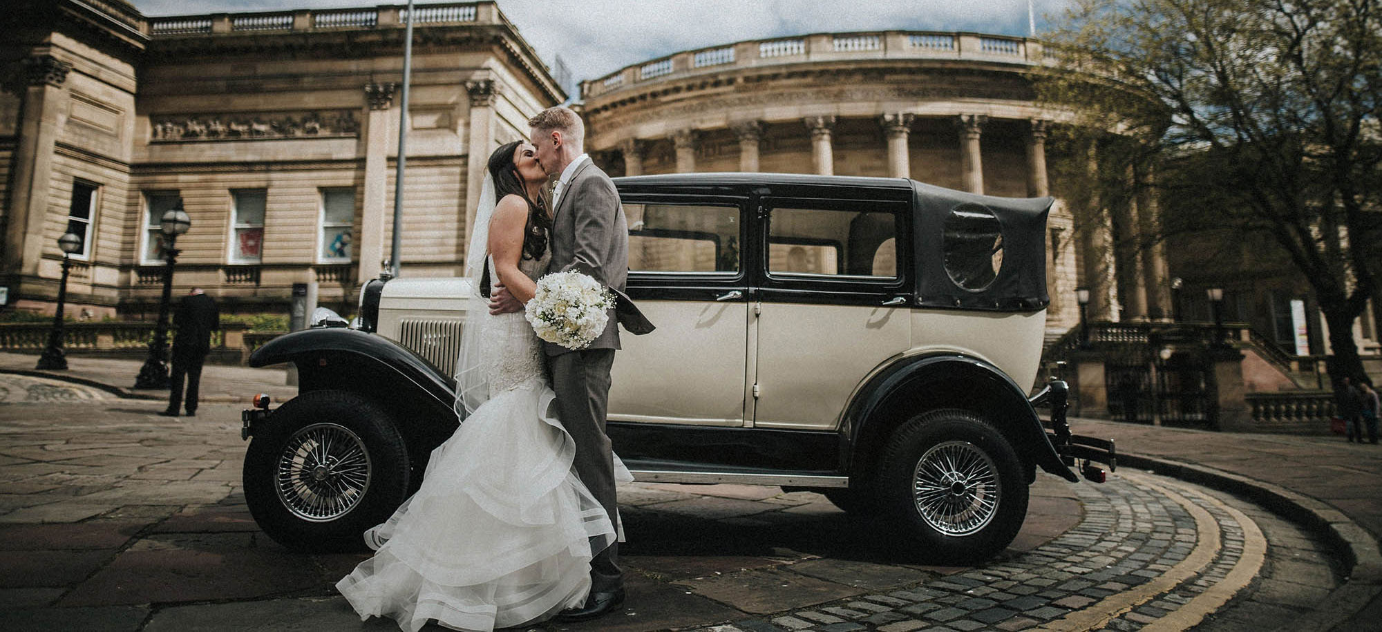 Wedded couple next to wedding car